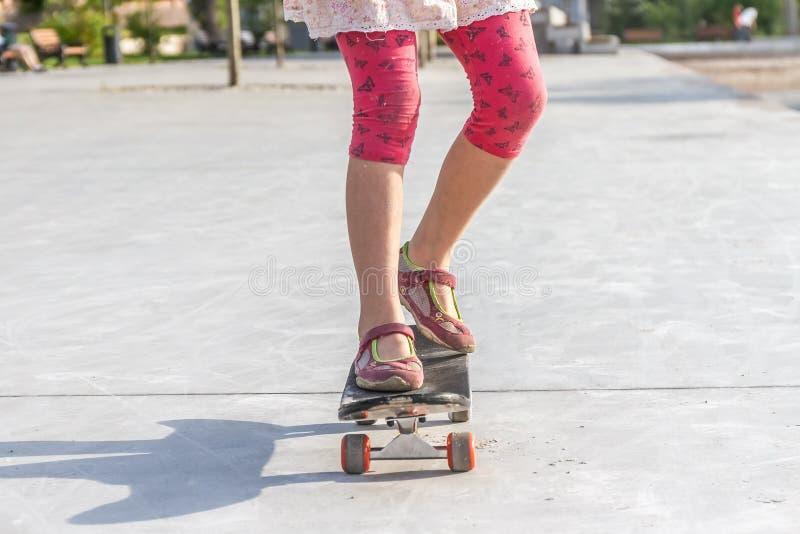 Schließen Sie oben von Mädchen ` s Füßen, die auf modernem kurzem Kreuzer skatebo stehen lizenzfreies stockbild