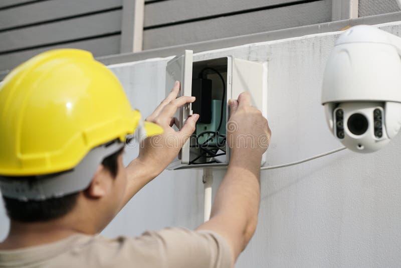 Schließen Sie oben von männlicher Techniker-Fixing-Überwachungskamera auf Wand stockbild