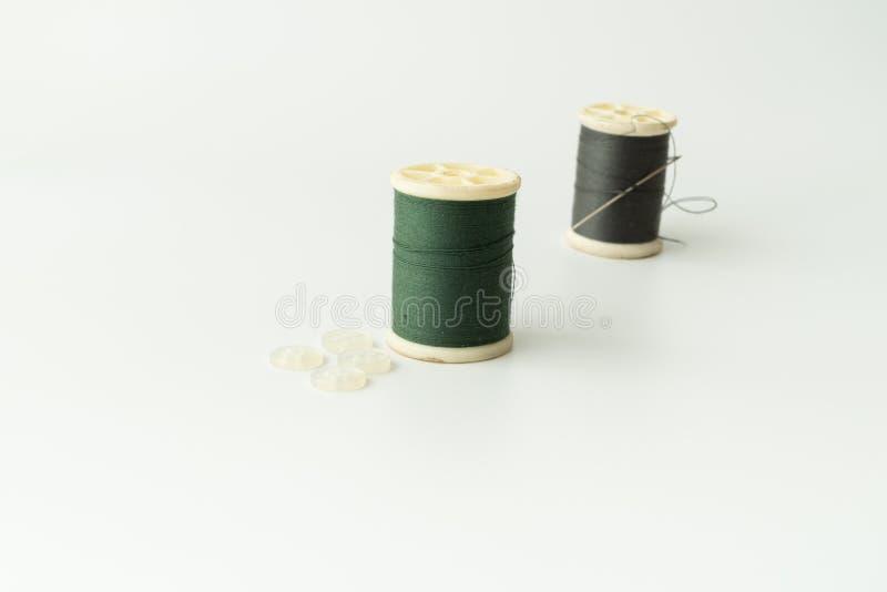 Schließen Sie oben von nähenden Einzelteilen, von der Spule des Threads, von der Nadel und vom Knopf lizenzfreie stockfotografie