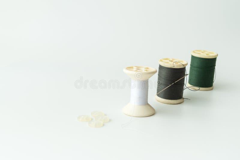 Schließen Sie oben von nähenden Einzelteilen, von der Spule des Threads, von der Nadel und vom Knopf lizenzfreie stockbilder