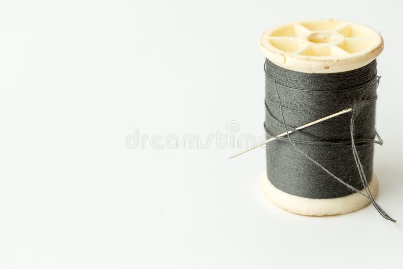 Schließen Sie oben von nähenden Einzelteilen, von der Spule des Threads, von der Nadel und vom Knopf lizenzfreie stockfotos