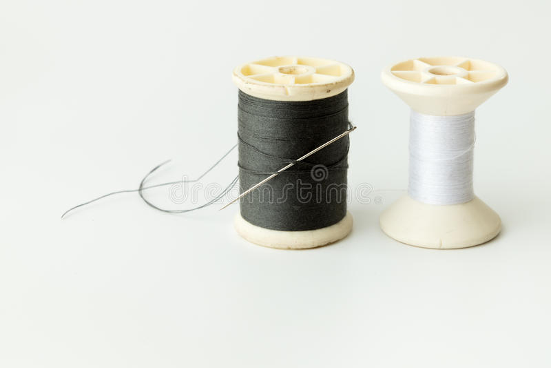 Schließen Sie oben von nähenden Einzelteilen, von der Spule des Threads, von der Nadel und vom Knopf stockfoto