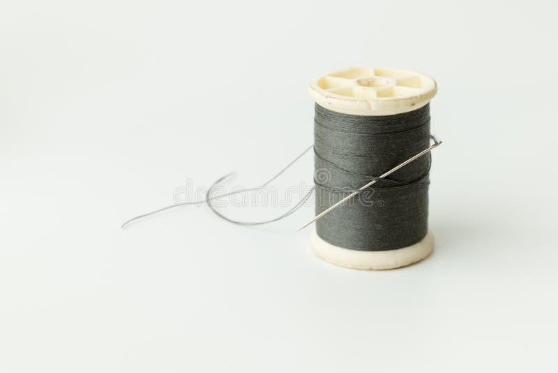 Schließen Sie oben von nähenden Einzelteilen, von der Spule des Threads, von der Nadel und vom Knopf stockfotos