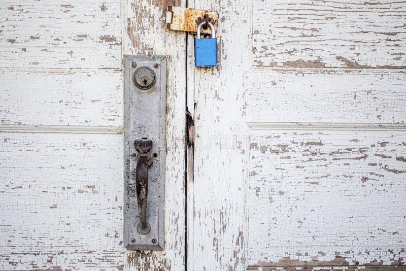 Schließen Sie oben von padlocked verwitterter hölzerner weißer Tür lizenzfreies stockbild