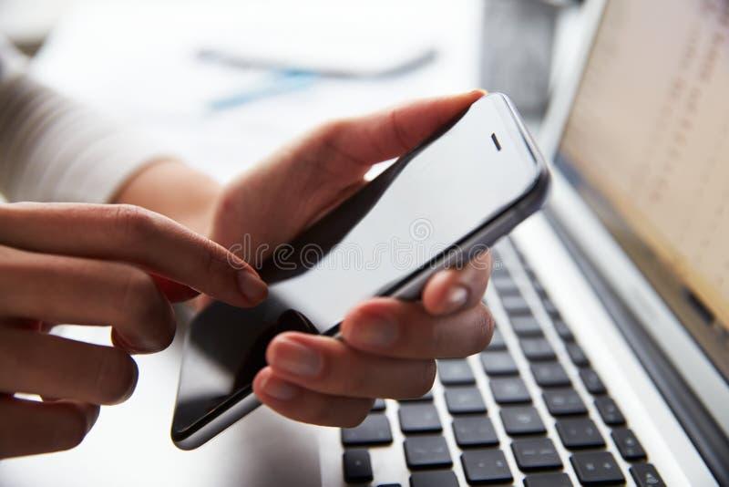 Schließen Sie oben von Person At Laptop Using Mobile-Telefon lizenzfreie stockfotos