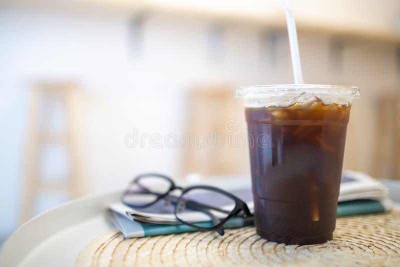Schließen Sie oben von, Plastikschale gefrorenen schwarzen Kaffee Americano auf Rundtisch mit Nachrichtenpapier und -Lesebrille i lizenzfreie stockfotos