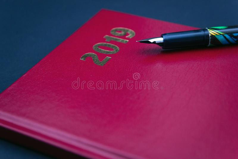 Schließen Sie oben von rotem ledernem Tagebuch 2019 mit Füllfederhalter lizenzfreie stockfotografie