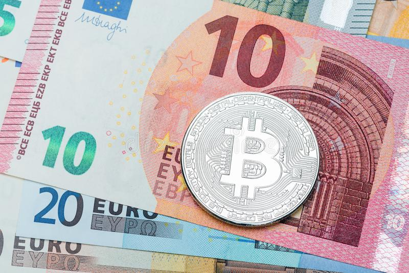 Schließen Sie oben von silbernem Bitcoin auf Eurowährungshintergrund Makro pH lizenzfreie stockbilder
