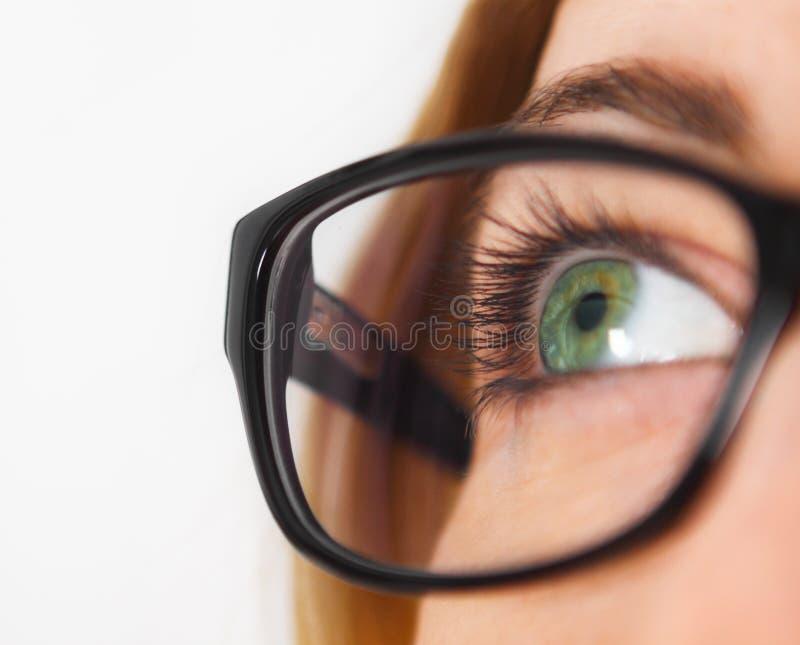 Schließen Sie oben von tragenden Gläsern des blauen Auges der Frau stockfoto