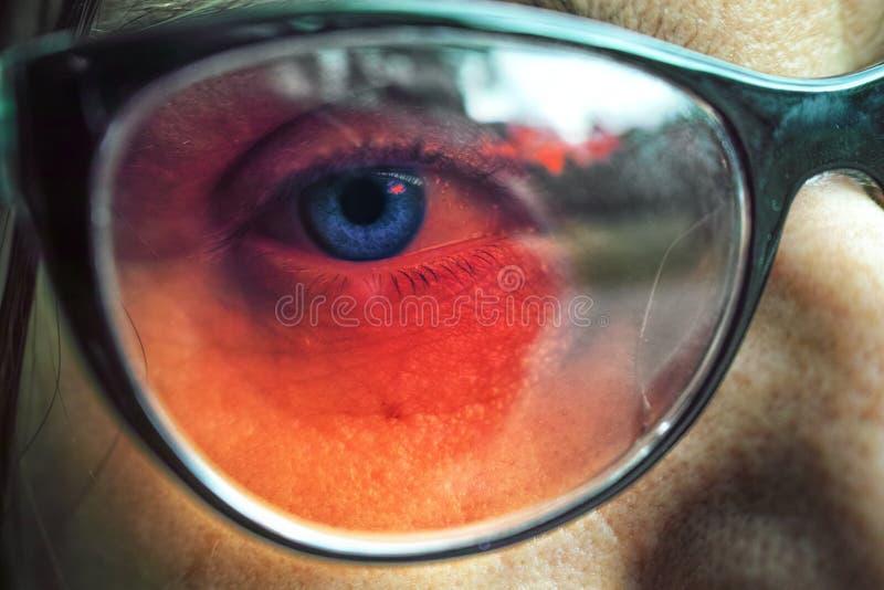 Schließen Sie oben von tragenden Gläsern des blauen Auges der Frau stockfotografie
