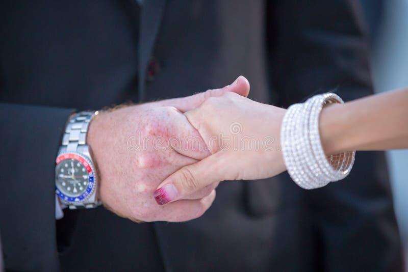Schließen Sie oben von umklammerten Händen der Braut und des Bräutigams zusammen während des Geistlichen stockfoto