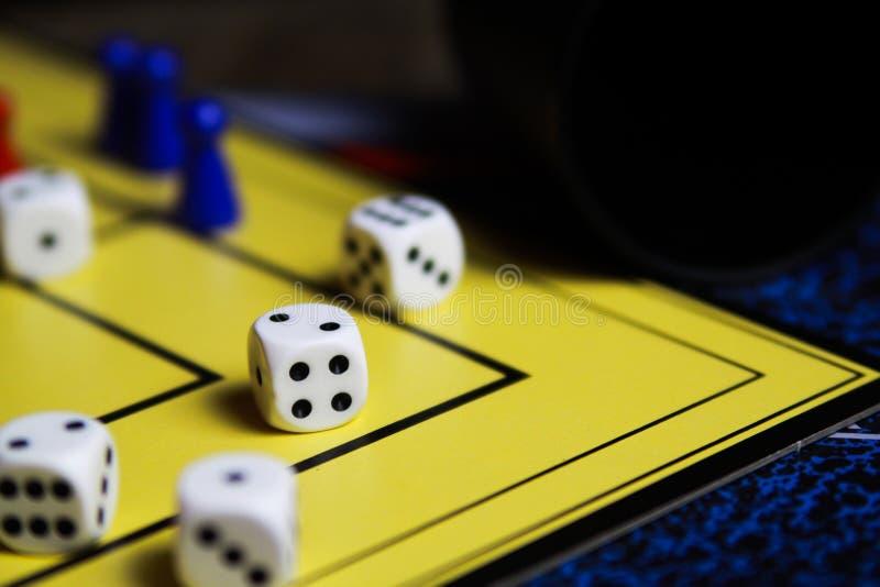 Schließen Sie oben von würfelt auf gelbem Spielbrett lizenzfreie stockbilder