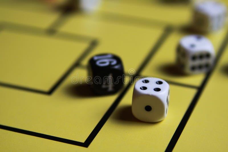 Schließen Sie oben von würfelt auf gelbem Spielbrett stockfotografie