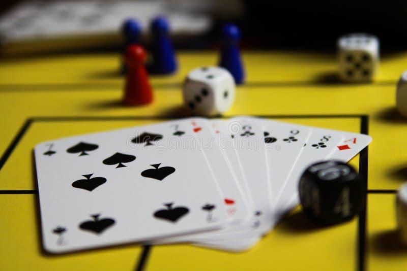 Schließen Sie oben von würfelt und kardiert auf gelbem Spielbrett lizenzfreie stockfotografie