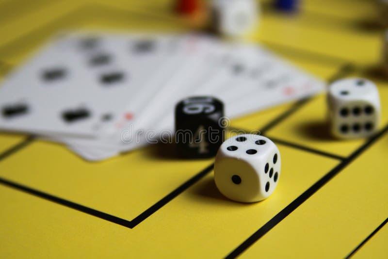 Schließen Sie oben von würfelt und kardiert auf gelbem Spielbrett stockfotos