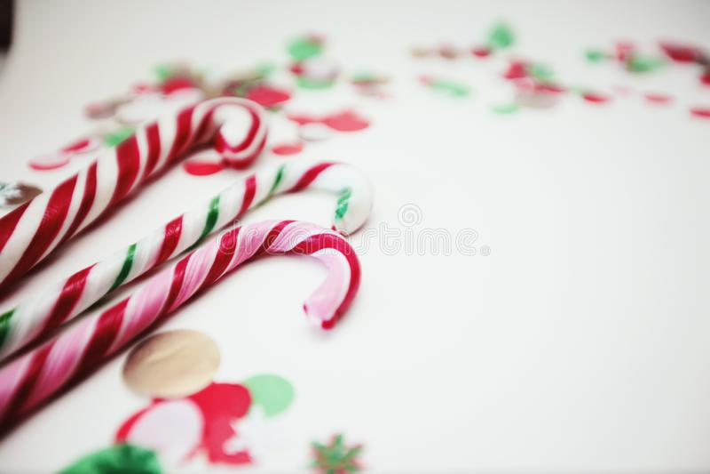 Schließen Sie oben von Weihnachtsgestreiften und farbigen Lutschern Süßigkeiten auf einem weißen Hintergrund mit Konfettis stockfotos