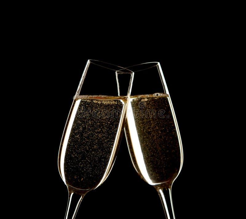 Schließen Sie oben von zwei Gläsern von Champagne klirrend zusammen lokalisiert auf Schwarzem stockfotografie