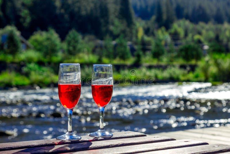Schließen Sie oben von zwei Glas Rotwein auf dem Hintergrund von einem Gebirgsfluss Hölzerner Wagenaufenthaltsraum, Berge, Luxusf lizenzfreie stockfotos