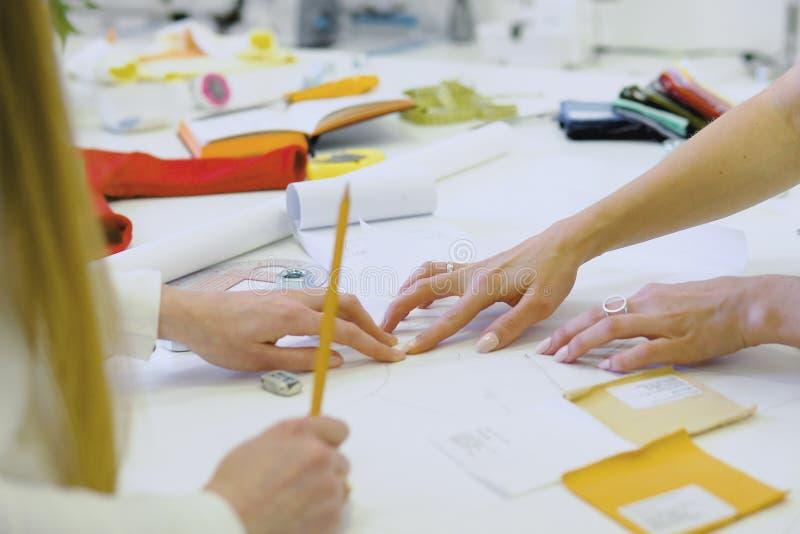 Schließen Sie oben von zwei jungen Frauen, die als Modedesigner und zeichnende Skizzen für Kleidung im Atelier arbeiten Geerntete stockfoto