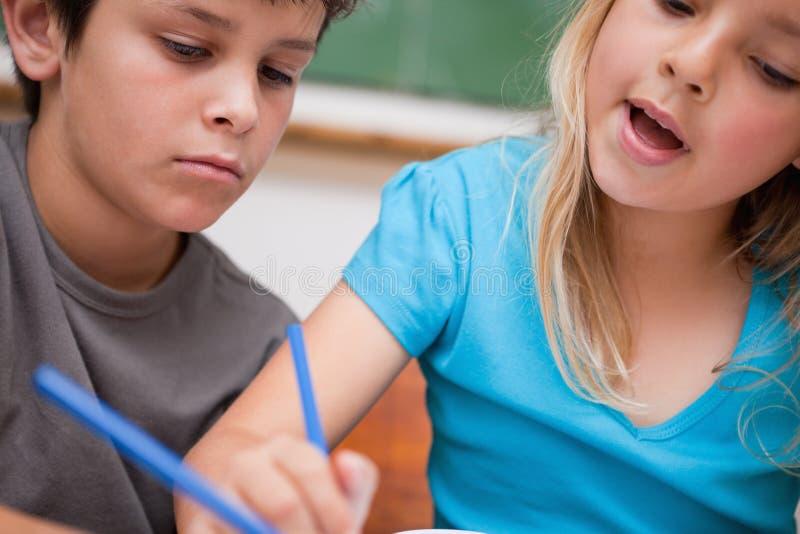 Schließen Sie oben von zwei Kinderdem schreiben stockbild