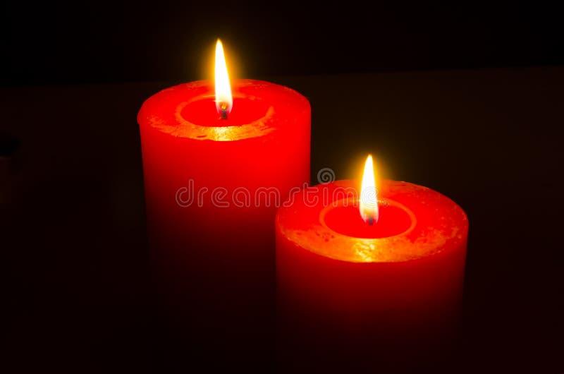Schließen Sie oben von zwei roten Kerzen lizenzfreies stockfoto