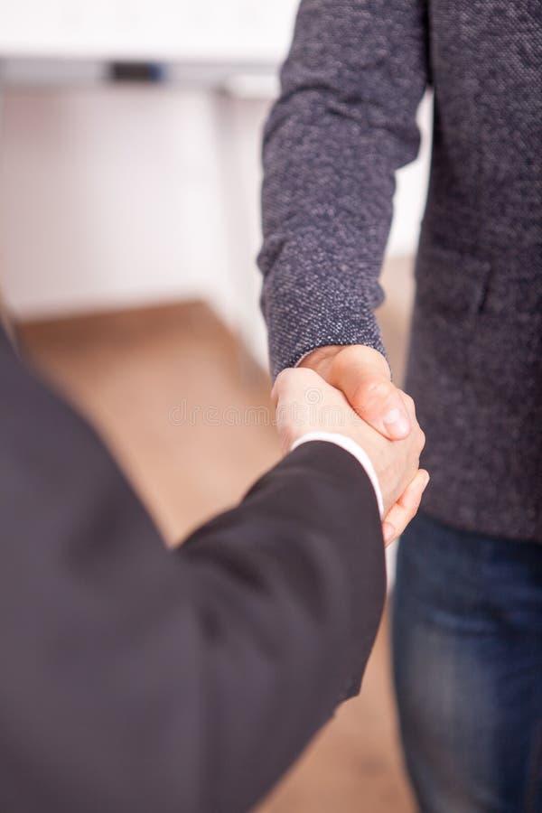 Schließen Sie oben von zwei Teilhabern, die Hände im Büro rütteln lizenzfreies stockbild