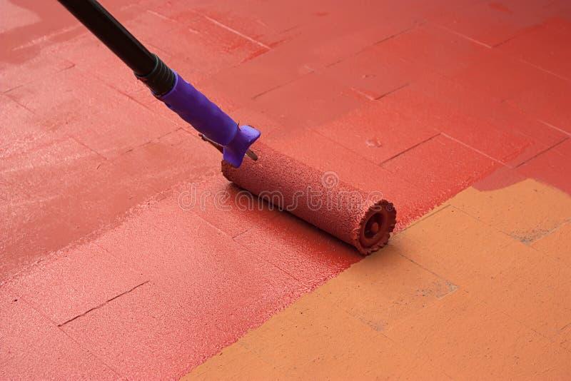 Schließen Sie Vertrag Malers ab, der einen Boden auf Farbrot malt lizenzfreies stockbild