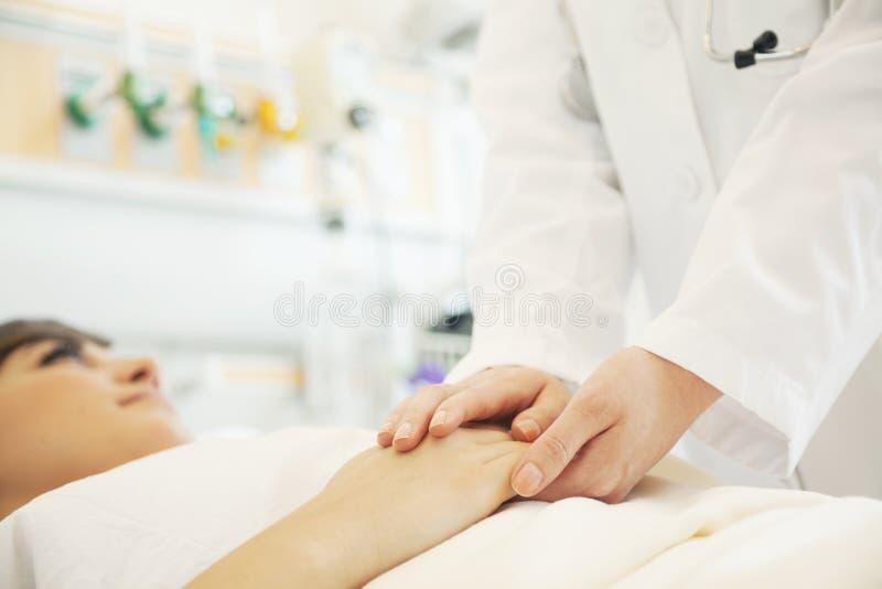 Schließen Sie von Doktor, der die Patientenhände hochhalten ist, die sich auf einem Krankenhausbett hinlegen lizenzfreies stockbild
