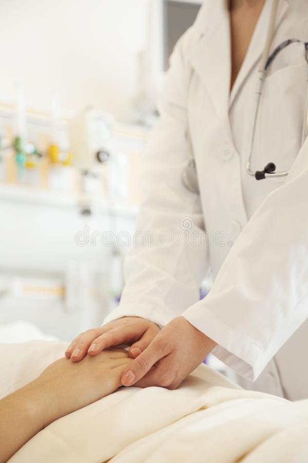 Schließen Sie von Doktor, der die Patientenhände hochhalten ist, die sich auf einem Krankenhausbett hinlegen stockfotografie