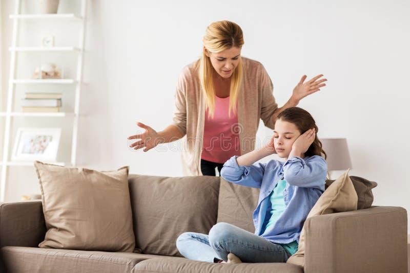 Schließend Ohren des Mädchens, zum der verärgerten Mutter nicht zu Hause zu hören stockfotografie