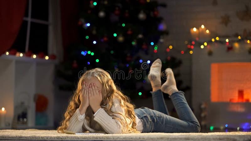 Schließendes Gesicht des Mädchens mit den Händen, die Wünsche machend und träumen von den Weihnachtsgeschenken lizenzfreie stockfotografie