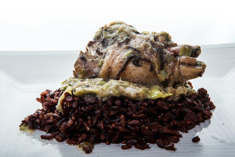 Schließung gegrillter Wachteln mit grüner Zwiebel auf wildem Reis lizenzfreie stockfotografie