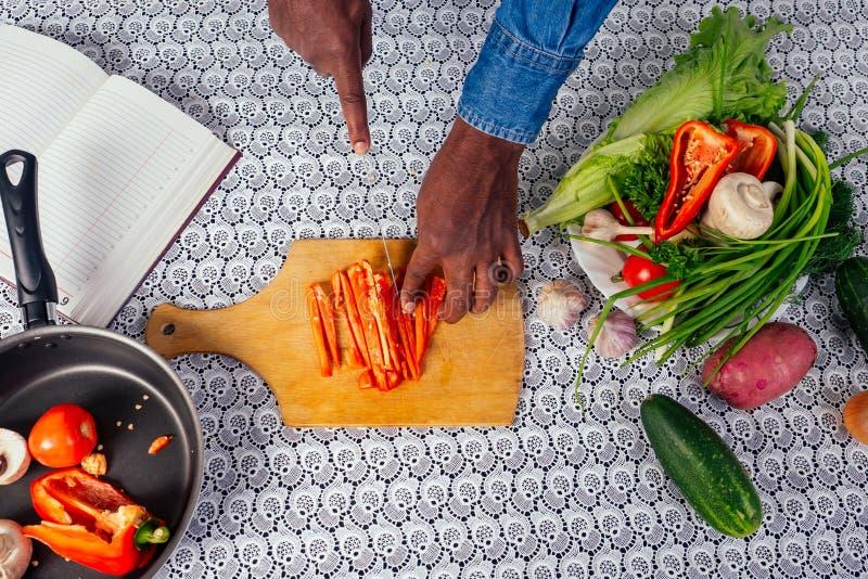Schließung von Mann Hand afrikanische Amerikaner schneidet Gemüse Salatpfeffer, Pilze, Tomate in Küche Rezept Buch auf der stockfotos
