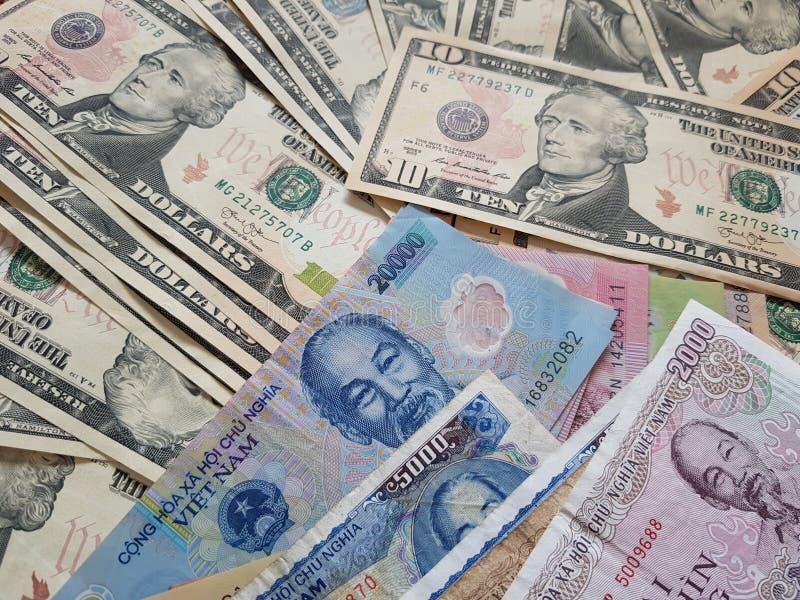 Schließen Sie herauf die Banknoten des Vietnamesen mit Ho Chi Minh ist Porträt und Vereinigter Staaten Dollar Fallender Dollar Ge stockfoto