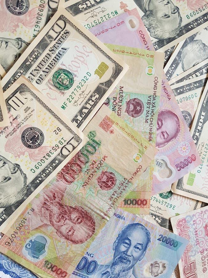Schließen Sie herauf die Banknoten von vietnamesischem Dong mit Ho Chi Minh ist Porträt und Vereinigter Staaten Dollar Fallender  lizenzfreies stockfoto