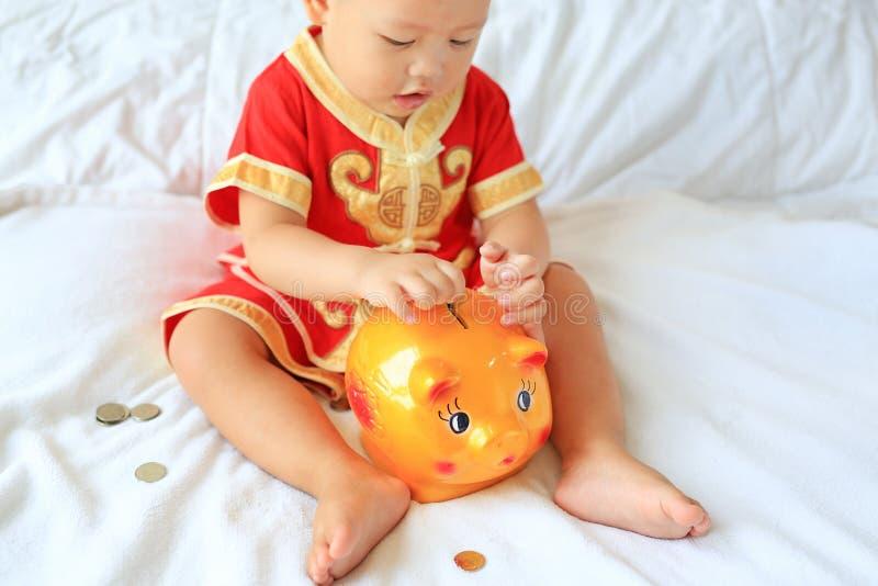 Schließen Sie herauf wenig asiatisches Baby im traditionellen chinesischen Kleid, das einige Münzen in ein Sparschwein setzt, das lizenzfreie stockfotos