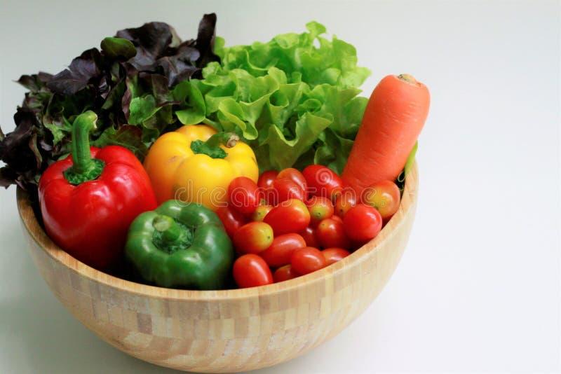 Schließen Sie oben vom Frischgemüse in einer hölzernen Schüssel, grüne Eiche, rote Eiche, Karotte, grüner Pfeffer, Kirschtomaten stockbilder