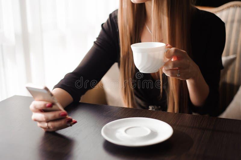 Schließen Sie oben von der Handfrau, die ihren Handy im Restaurant, Café verwendet lizenzfreie stockfotografie