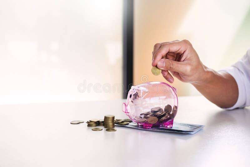 Schlie?en Sie oben vom Gesch?ftsmann, der M?nze in kleines Sparschwein, das Konzept des Einsparungsgeldes und Investition setzt stockfoto