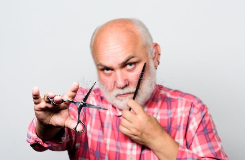 Schlie?en Sie oben vom Mannrasieren Rasieren des Scherentool-kit schneiden Sie und Bürstenhaar reifer bärtiger Mann lokalisiert a stockfotografie
