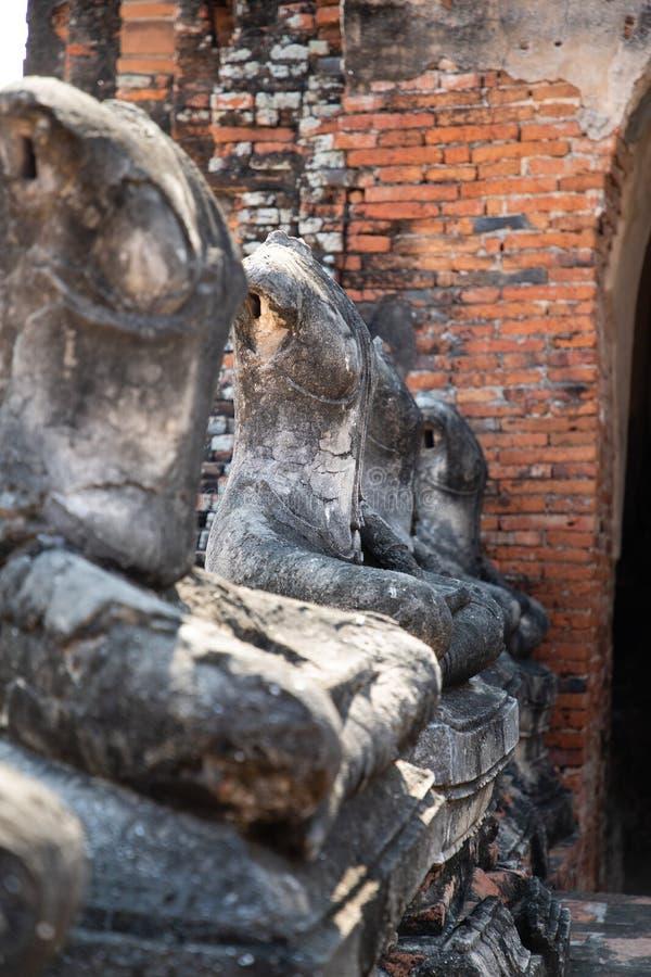 Schlie?en Sie oben von alten Steinbuddha-Statuen, die in Linie im ruinierten Tempel in Ayutthaya gelegt werden stockfotos