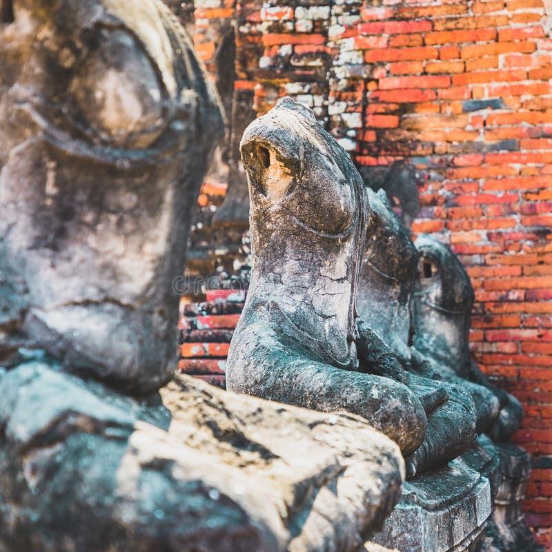 Schlie?en Sie oben von alten Steinbuddha-Statuen, die in Linie im ruinierten Tempel in Ayutthaya gelegt werden lizenzfreies stockfoto