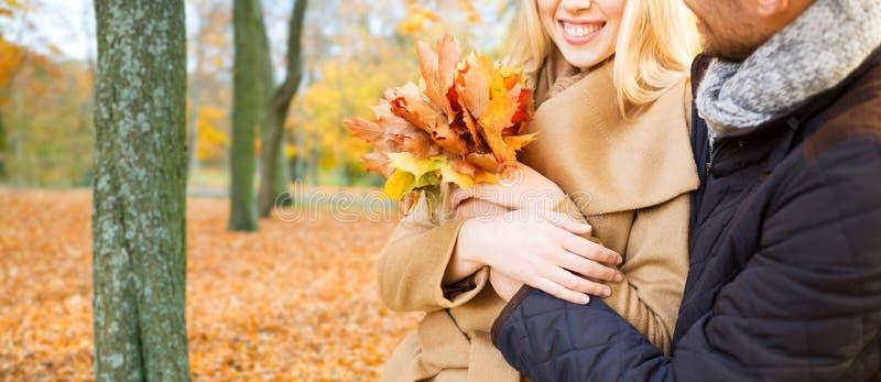 Schlie?en Sie oben von den l?chelnden Paaren, die im Herbstpark umarmen stockfotos