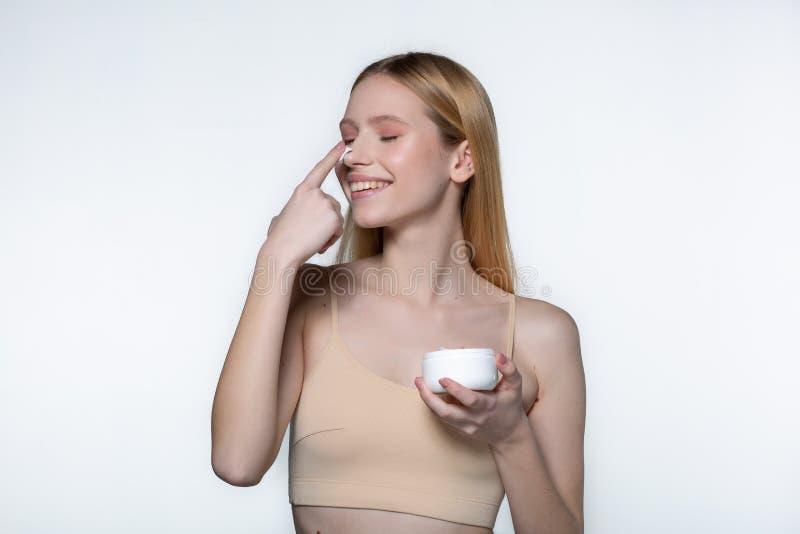 Schlie?en Sie oben von der positiven jungen Frau mit dem blonden mit einem Glas Creme in ihrer Hand stehenden und beim Setzen l?c stockbild
