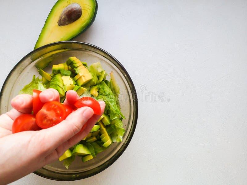 Schlie?en Sie oben von der weiblichen Chefhand, die Fetaw?rfel auf griechischen Tomatensalat des strengen Vegetariers mit Oliven  lizenzfreie stockbilder