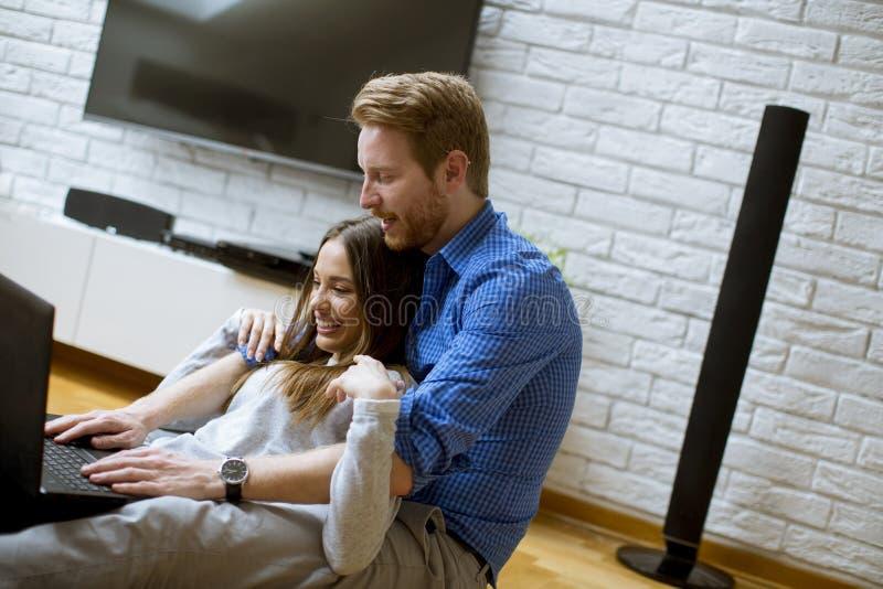 Schlie?en Sie oben von einem Paar unter Verwendung eines Notizbuches beim Sitzen auf dem Boden in ihrem Wohnzimmer stockbild