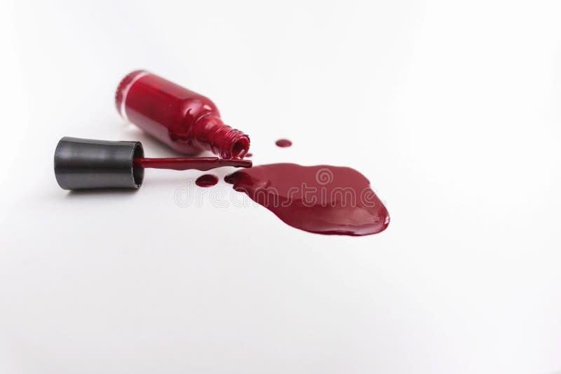 Schlie?en Sie oben von einer roten Nagellackflasche und -tropfen auf wei?em Hintergrund lizenzfreie stockfotografie