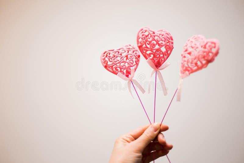 Schlie?en Sie oben von rosa sch?nem Herzen drei mit Mustern auf der Hand des M?dchens auf wei?em Hintergrund lizenzfreie stockfotografie