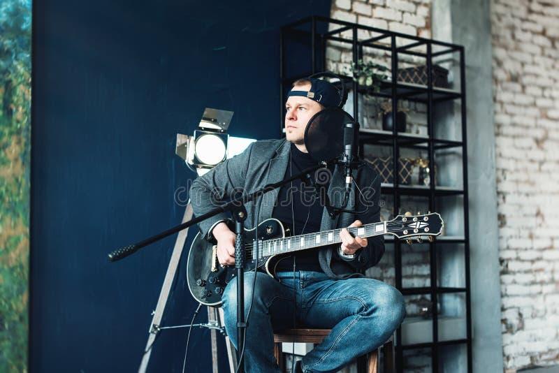 Schlie?en Sie von einem Manns?nger auf einem Schemel in, der Kopfh?rern mit einer Gitarre oben sitzen ist, die eine Bahn in einem lizenzfreies stockbild