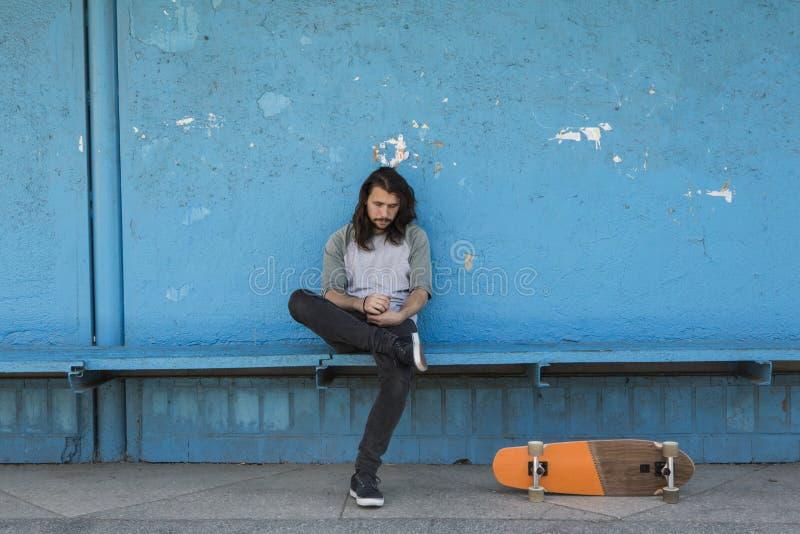 Schlittschuhläufer, der auf blauem Hintergrund mit einem orange Skateboard nahe ihm sitzt lizenzfreie stockbilder